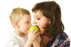 Mother and son eating apple. Mother and son eating green apple Royalty Free Stock Photo