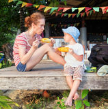 Mother and a son eating corn outdoors Royalty Free Stock Photography
