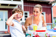 Mother with son eating fruit cake in front of house Stock Photography