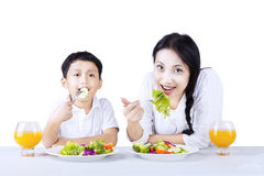 Mother and son eating healthy salad - isolated Stock Photo