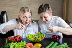 Mother and son eating salad and having fun. Royalty Free Stock Photo