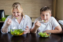 Mother and son eating salad and having fun. Stock Photos