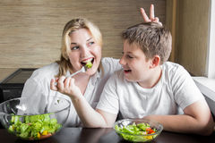 Mother and son eating salad and having fun. Royalty Free Stock Photography
