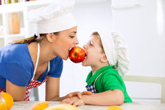 Mother and son eating together red fresh apple Stock Photo