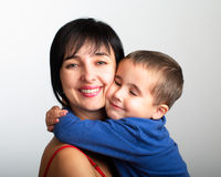 Mother and son embrace. Portrait of mother and son embrace on grey gradien background Stock Photo