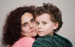 Mother and son embracing. Each other. Indoor scene stock photo