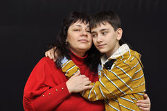 Mother and son are embracing each other. Over black stock photography