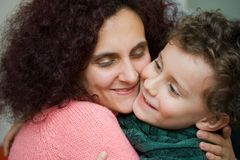 Mother and son embracing each other. Indoor scene stock image
