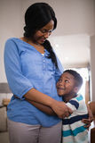 Mother and son embracing at home. Smiling mother and son embracing at home stock image