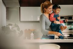Mother and son enjoying while baking cookies in kitchen. Smiling women holding his son in her arms while making cookies in kitchen. Female with a cute little boy stock photos