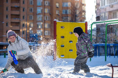 Mother and son enjoying beautiful winter day outdoors, playing with snow in city Stock Photo