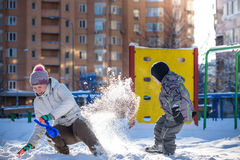 Mother and son enjoying beautiful winter day outdoors, playing with snow in city Stock Photos