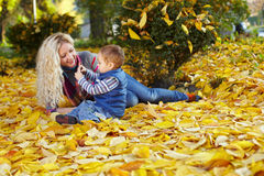 Mother and son on fallen leaves in autumn park. Attractive curly mother and son sitting on the carpet of fallen leaves in autumn park Royalty Free Stock Photography