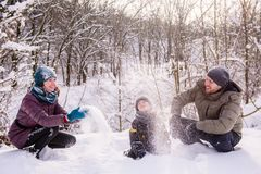 Happy family throw snow in winter forest royalty free stock image