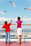 Mother and son feed seagulls on deck of ship. Royalty Free Stock Photography
