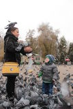 Mother and son feeding the birds in Almaty Royalty Free Stock Photos