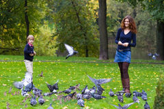 Mother and son feeding pigeons in a park Stock Photos