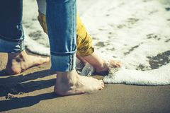 Mother and son with feet in the shore water. Love and protection. Royalty Free Stock Photo