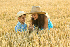 Mother and son in a field of wheat playing Stock Image
