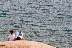 Mother and son fishing. A mother and son spend a lazy afternoon on a warm rock by the side of a lake doing some casual fishing Stock Images