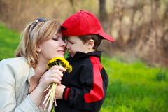 Mother and son with flowers. Cute little boy in red cap gives yellow dandelion to mother at outdoor royalty free stock image