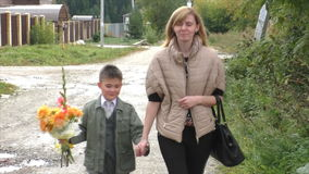Mother and son go on the road with a bouquet stock video