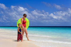 Mother and son go swimming at tropical beach Royalty Free Stock Photo