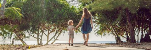 Mother and son go to the sea beach. Resort vacation on tropical beach. Path to beach BANNER, long format stock images