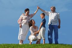 Mother and son, grandparents making house roof. Mother and son holding for hands, grandparents making house roof gesture, summer lawn stock photo