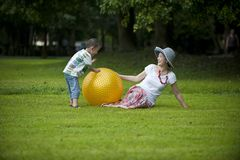 Mother and son in grass and play ball Royalty Free Stock Image