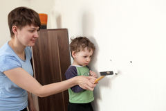 Mother and son with hammer Stock Photos