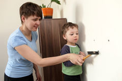 Mother with son hammering plastic anchor. Mother with her son hammering plastic anchor into wall at home Stock Image