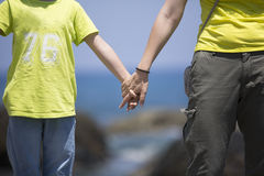 Mother and son hand in hand at seaside Stock Photo
