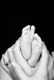 Mother and son hands and feet. Mother holds the feet of her newborn son. Black and white with space for your text Stock Photography