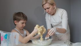 Mother and son hands knead the cookie dough.  stock video footage