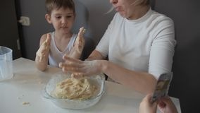 Mother and son hands knead the cookie dough stock footage