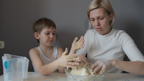 Mother and son hands knead the cookie dough.  stock video