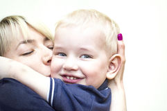 Mother And Son. Happy mother with eyes shut hugging and kissing her little son who looking at camera royalty free stock photography