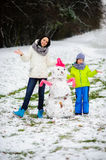 Mother with son have built a snowman. Royalty Free Stock Photography