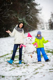 Mother with son have built a snowman. Stock Photo