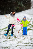 Mother with son have built a snowman. Royalty Free Stock Images