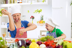 Mother and son have fun in kitchen food war Stock Image