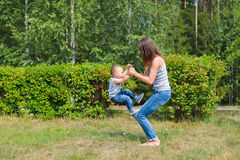 Mother and son have fun playing in park. Littkek kid making steps upwards over moms legs