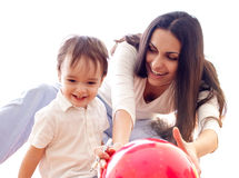 Mother and son have fun with red balloon together. Isolated on white (focus is on mother Royalty Free Stock Image