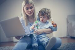 Mother and son have play together, Mom using laptop. Childhood Royalty Free Stock Photography