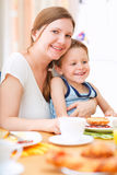 Mother and son having breakfast. Vertical portrait of happy mother and son having breakfast together stock photography