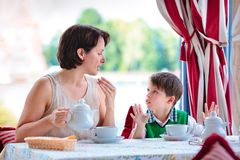 Mother and son having breakfast together. At cafe Stock Photos