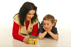 Mother and son having conversation. Mother and son lying down on floor in their home and having conversation about a new house Stock Image