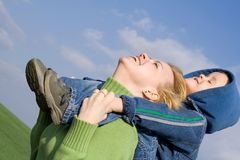 Mother and son having fun. On the green spring field under a sunny sky stock image