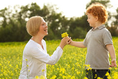 Mother and Son Having Fun. Son giving flowers to his mother. outdoor shot Royalty Free Stock Photo